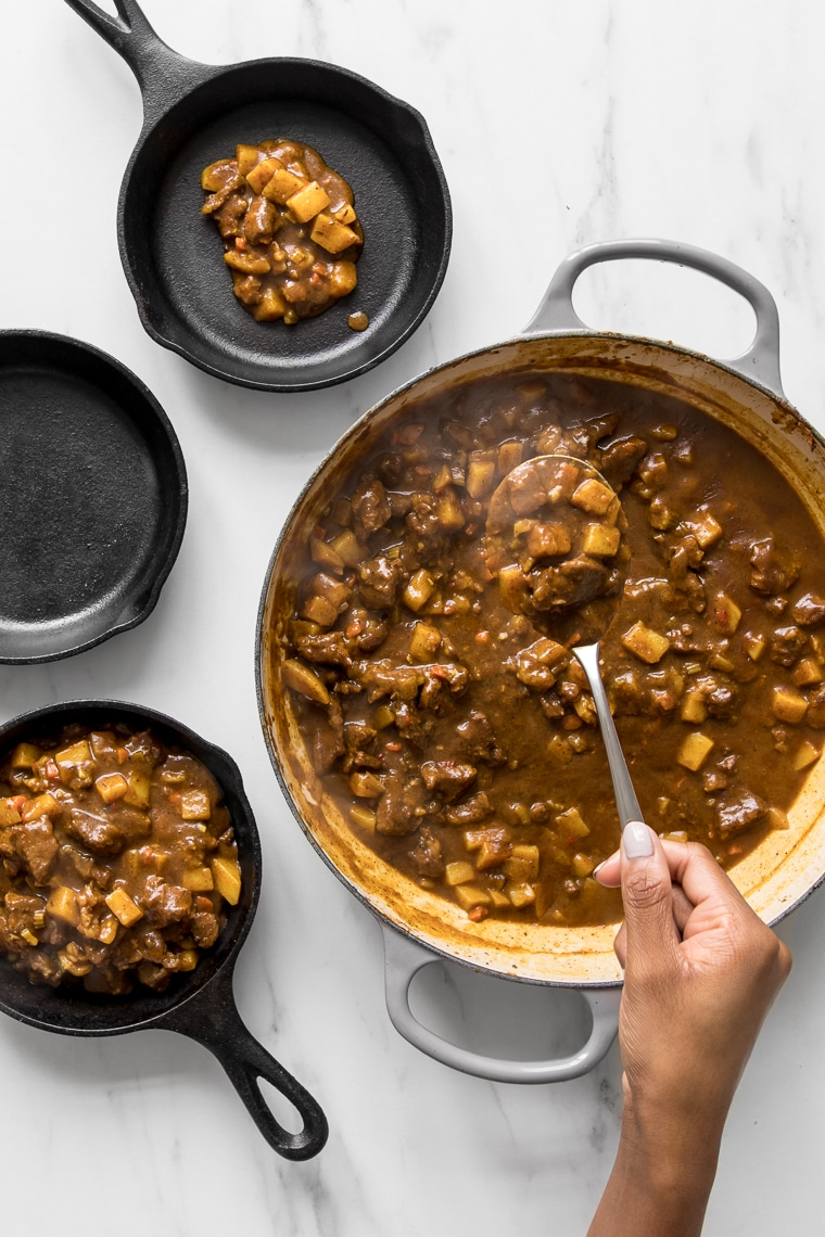 Spooning curry beef filling into small skillets