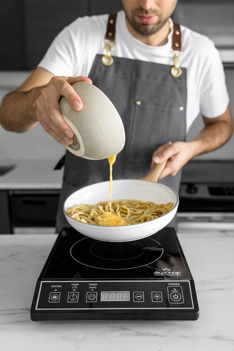Pouring eggs into the pasta for spaghetti carbonara