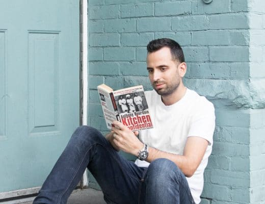 Reading on of the top 5 books by chefs leaning against a brick wall