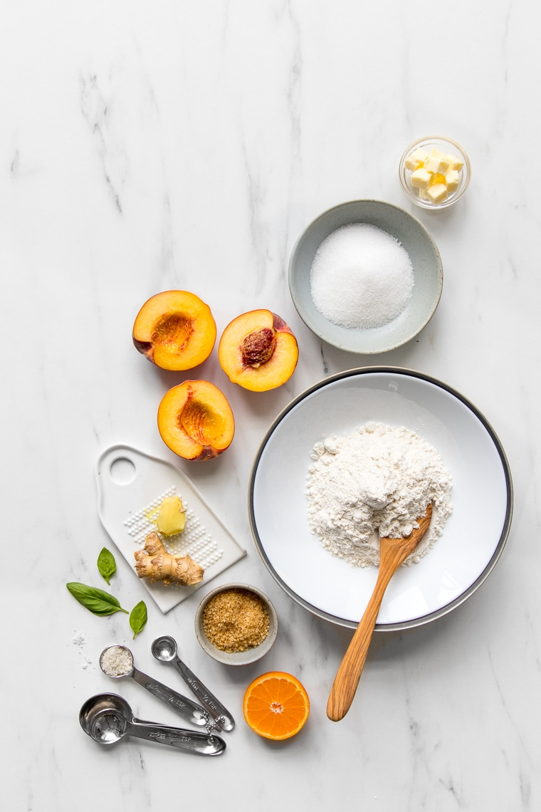 Ingredients for peach galette laid out on marble table
