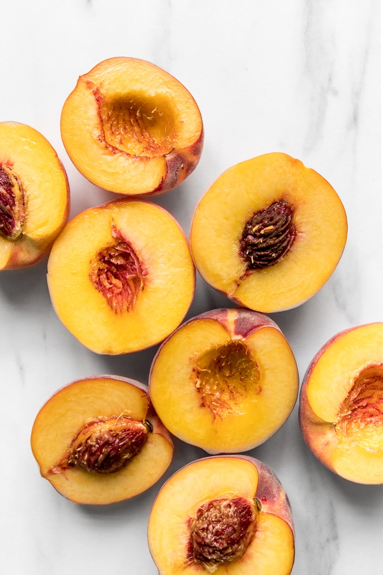Peach halves on a marble table