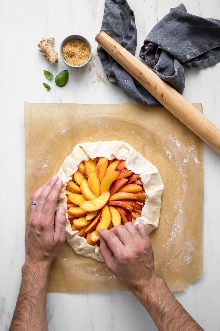 Folding the crust of a peach galette