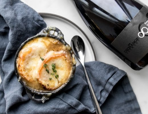 The Best French Onion Soup on a blue napkin next to a large bottle of beer