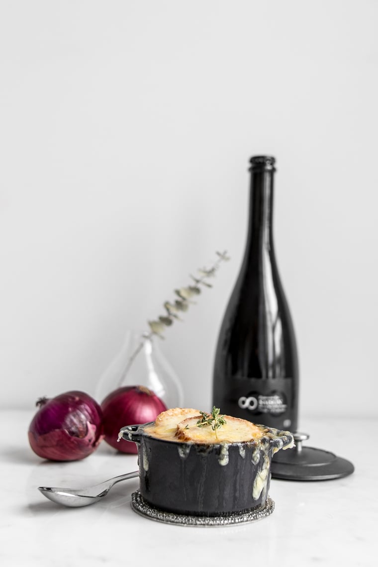 The Best French Onion Soup with two red onions and a bottle of beer behind it