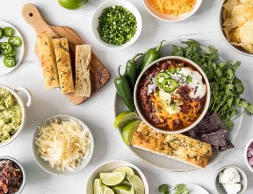 Bowl of homemade chili in the middle of a chili bar with bread, avocado, onions, cheese, limes, sour cream and chips