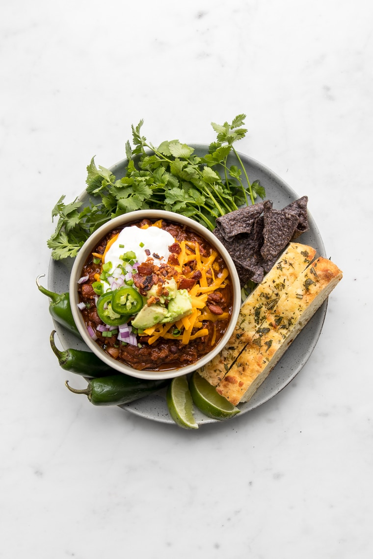 Overhead of a bowl of chili topped with cheese, sour cream, and jalapenos, surrounded by bread, cilantro and tortilla chips