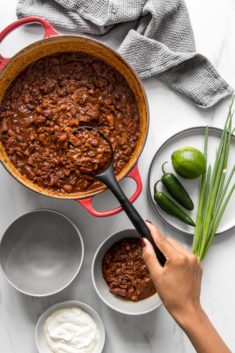 Homemade chili being served from the pot into bowls
