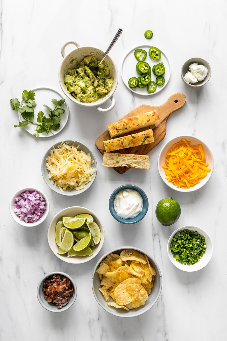 Overhead image of various bowls of toppings for the chili bar