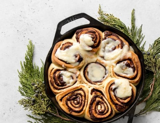 Chocolate rolls with cream cheese frosting in a skillet on top of cedar branches