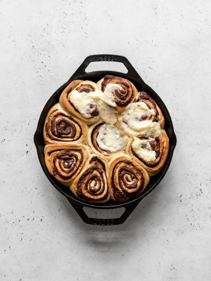 Baked chocolate rolls in a skillet with cream cheese frosting