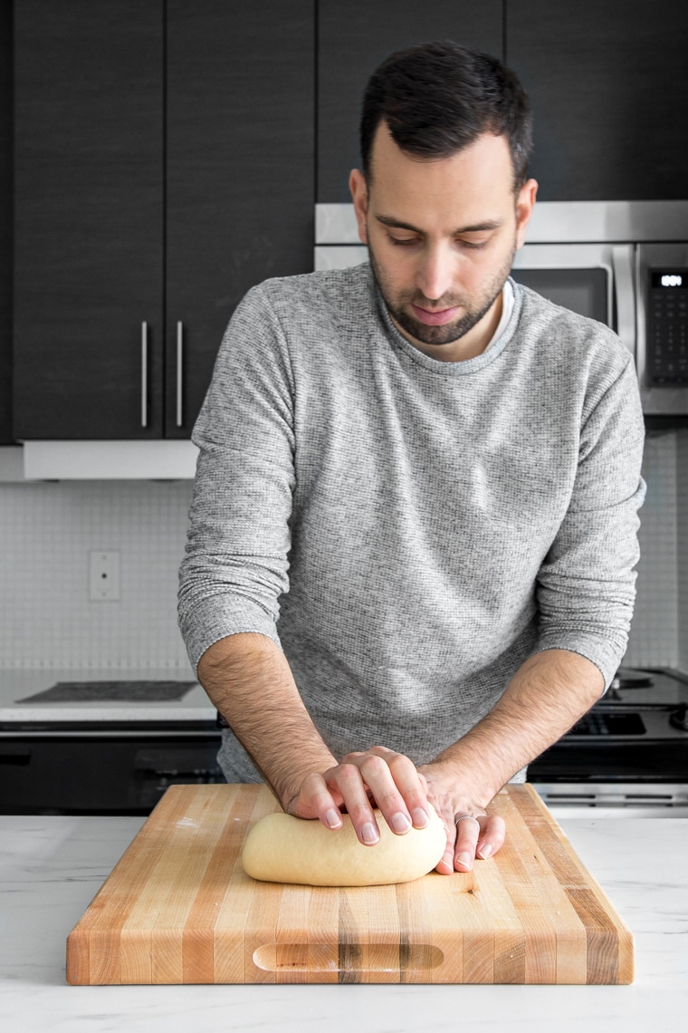 Kneading dough on a wooden cutting board