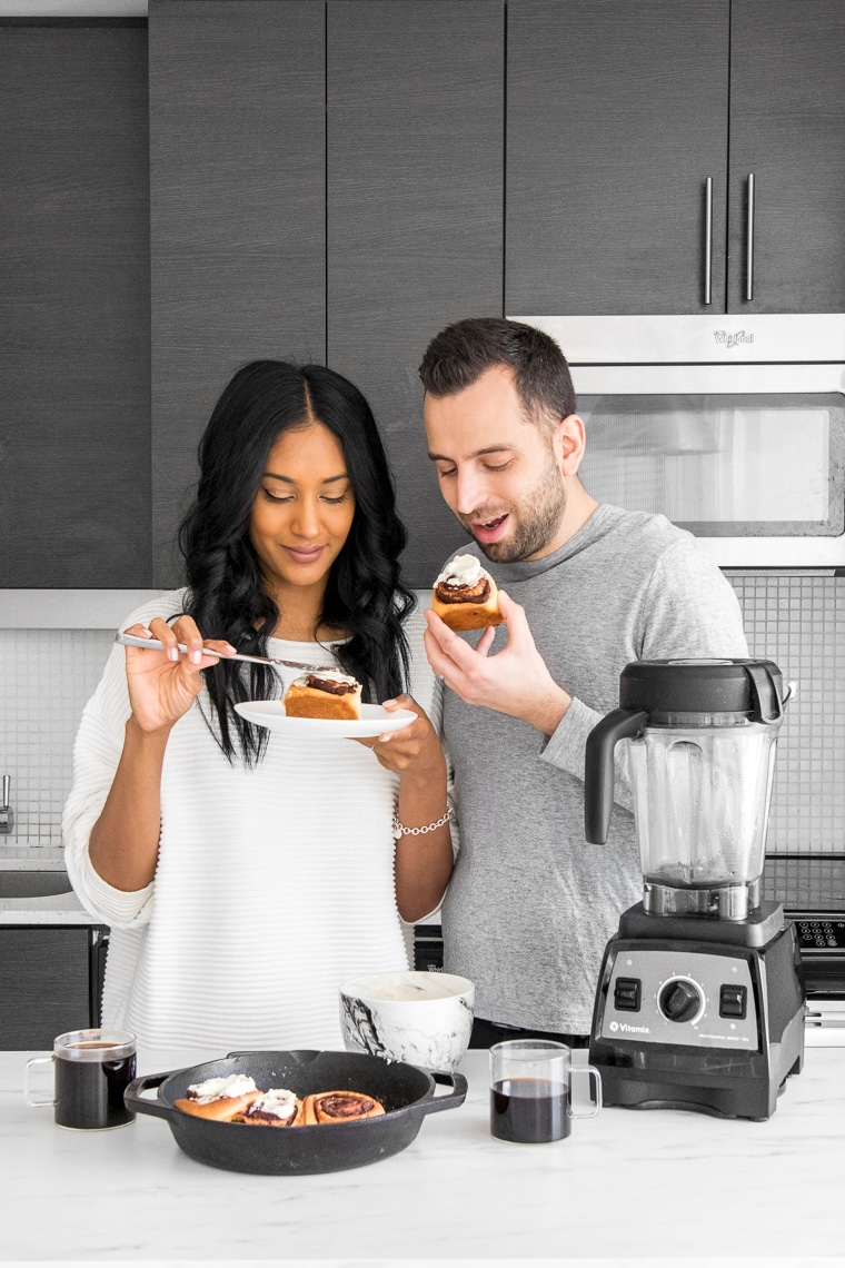 Couple eating chocolate rolls with cream cheese frosting in a kitchen with a Vitamix