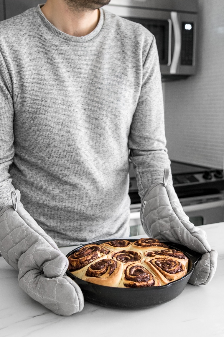 Holding the skillet with the freshly baked chocolate rolls