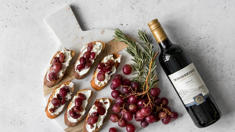 Grape and goat cheese crostini on a marble and wood board with grapes and a red wine bottle