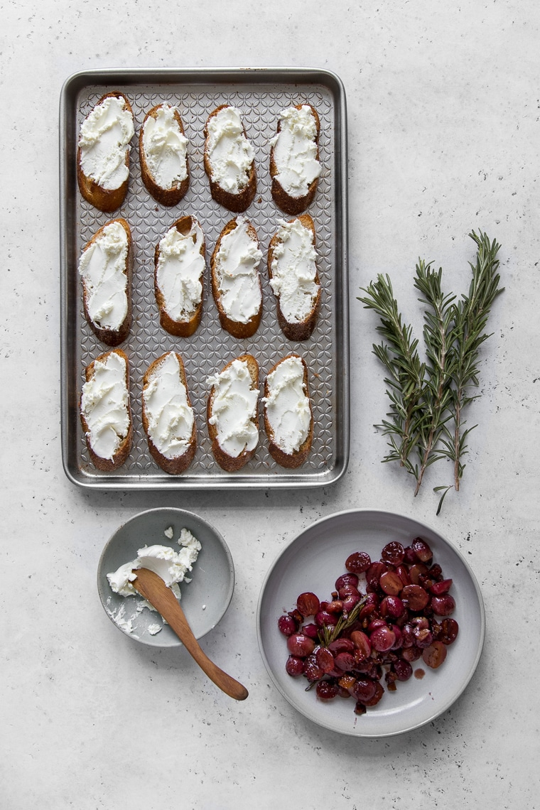 Baguette toast on a baking sheet with goat cheese next to frying pan of cooked grapes