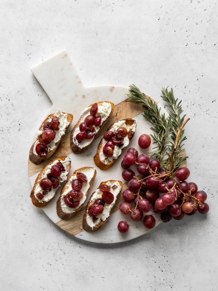 Grape and goat cheese crostini on a marble and wood board with grapes
