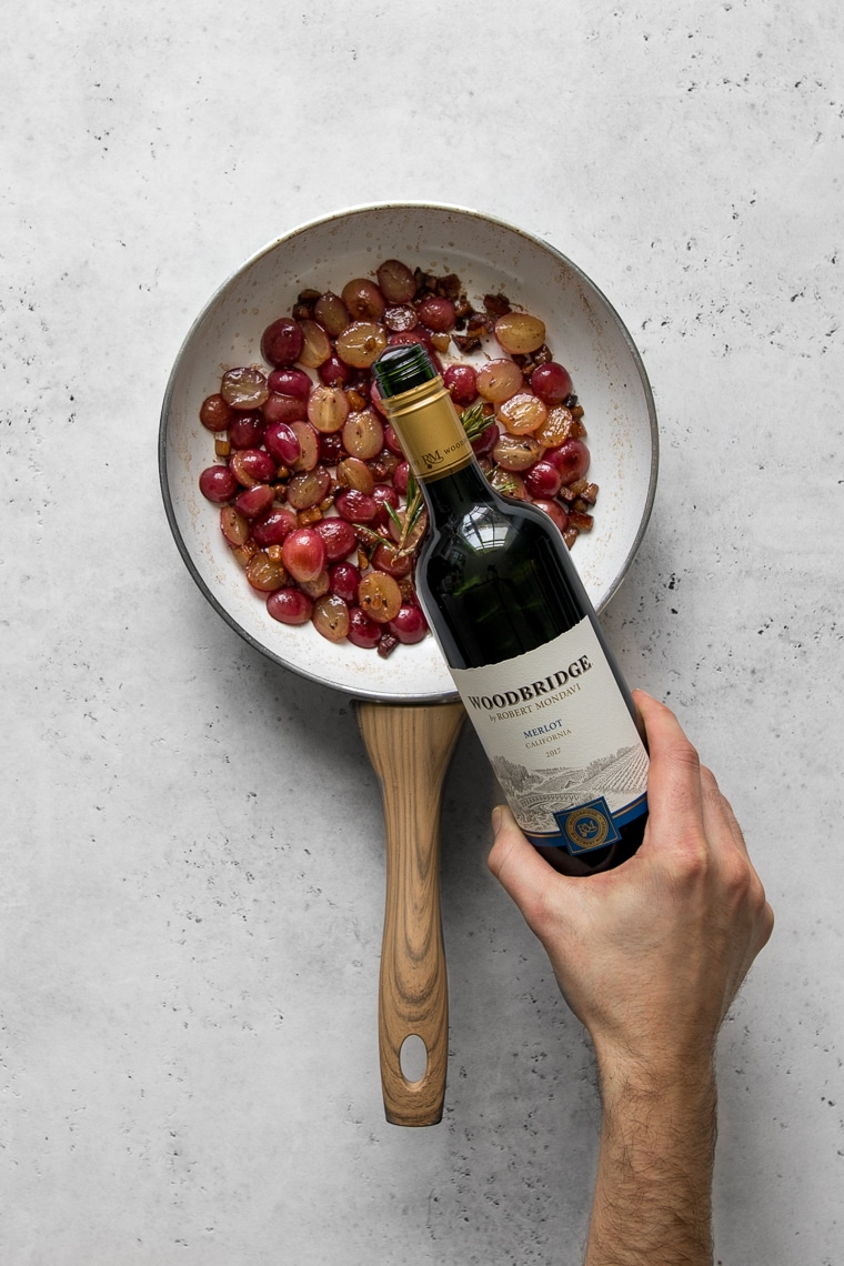 Pouring wine into the frying pan of grapes