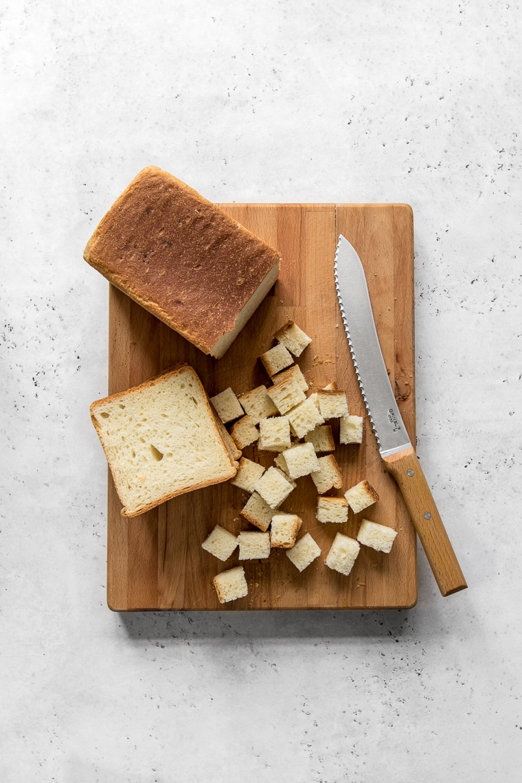 Loaf of bread on a cutting board being cut into cubes