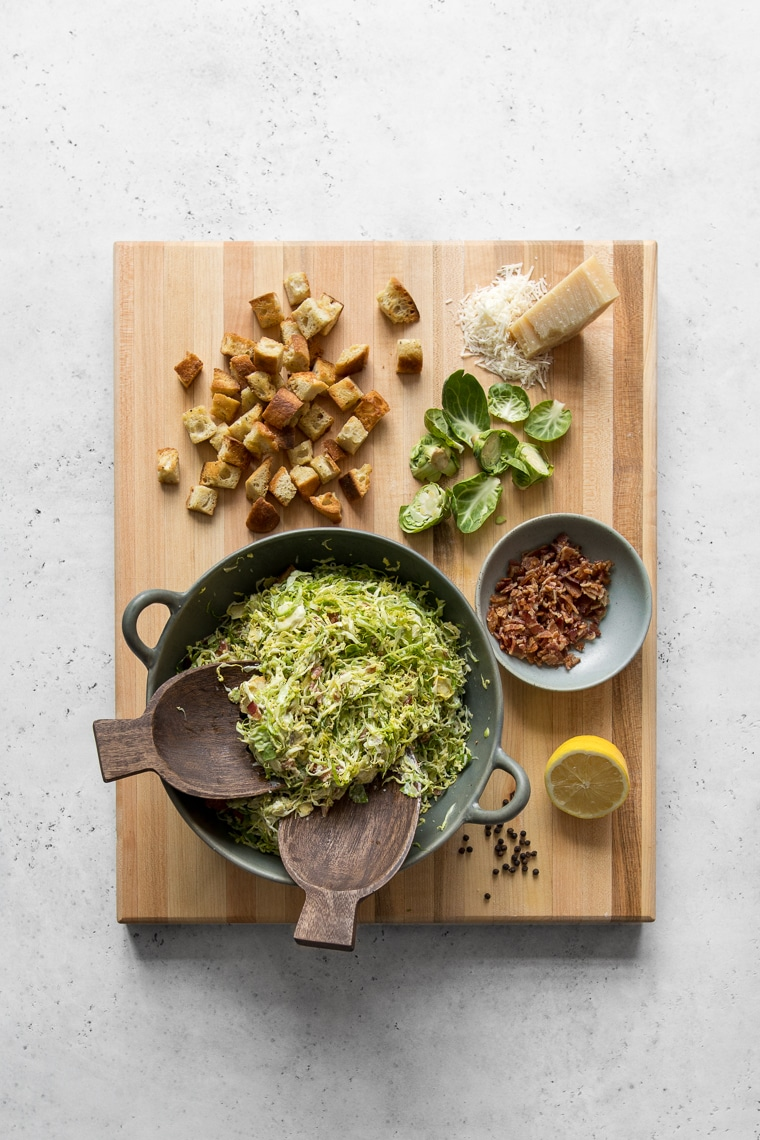 Large Cutting Board with Bowl of Brussels Sprout Salad, croutons, bacon, lemon, and Parmingianno-Reggiano