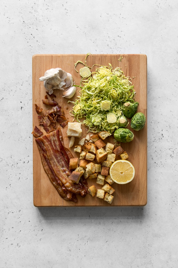 Cutting board with croutons, bacon, lemon, garlic, and brussels sprouts