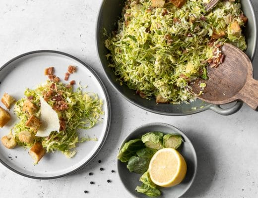 Bowl of Brussels Sprout Caesar Salad, plate of Brussles Sprout Caesar Salad and bowl with lemon
