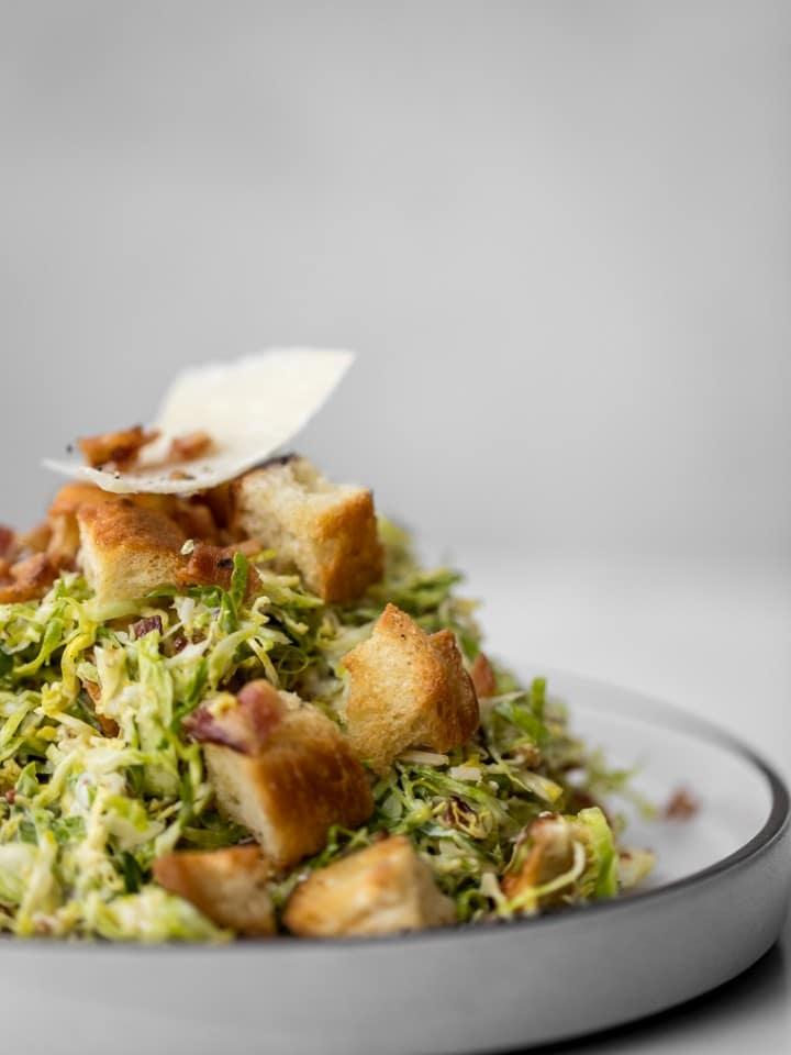 Side shot of Brussels Sprout Caesar Salad on a Plate