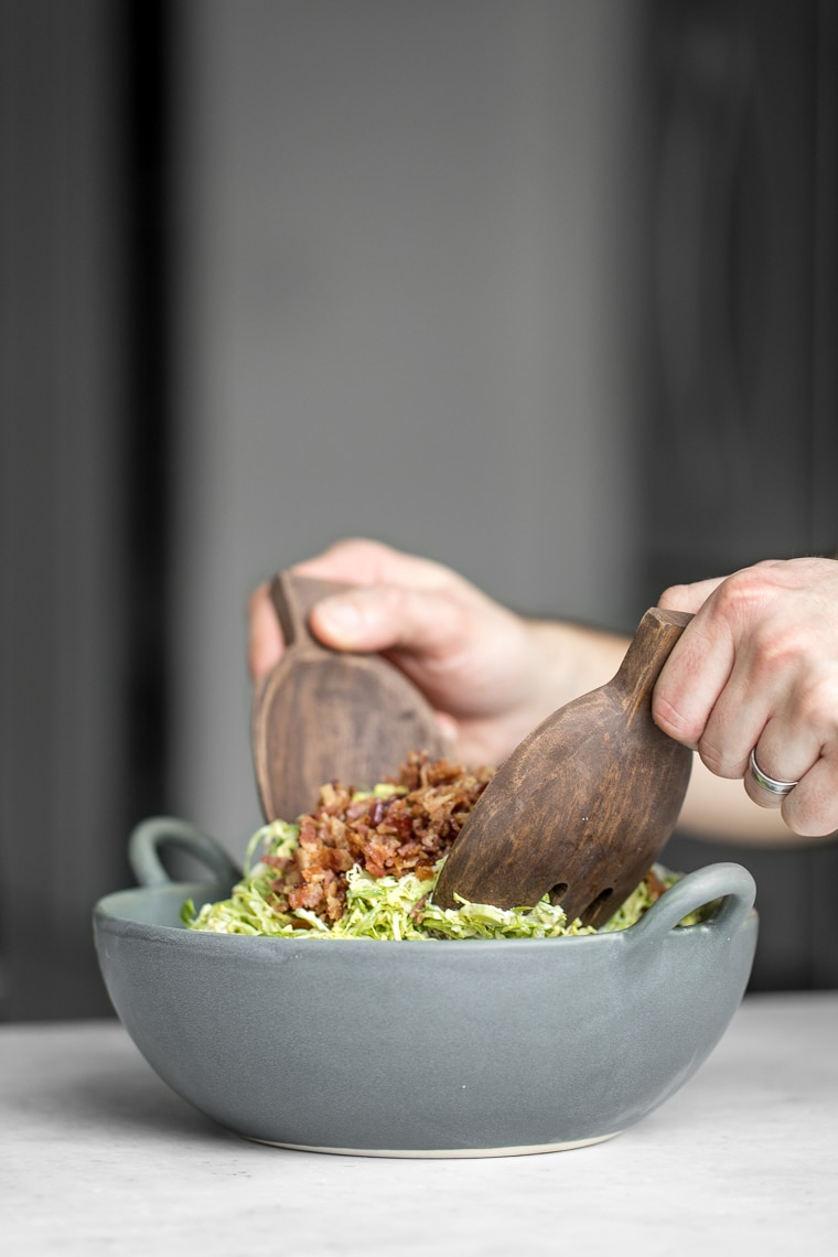 Tossing a salad in a grey bowl with wooded salad tongs