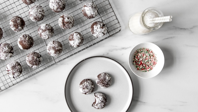 Chocolate Crinkle Cookies with milk and small bowl of crushed candy canes