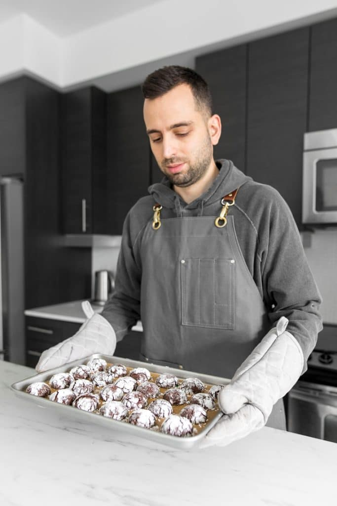 Chef holding the finished Double Chocolate Crinkle Cookies with Candy Cane fresh from the oven
