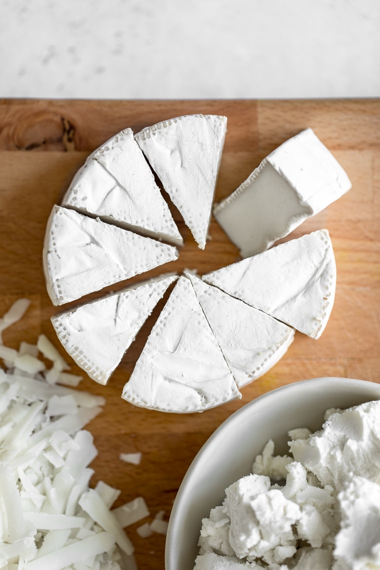 Close up of brie cheese cut in wedges, crumbled goat cheese, and grated white cheese
