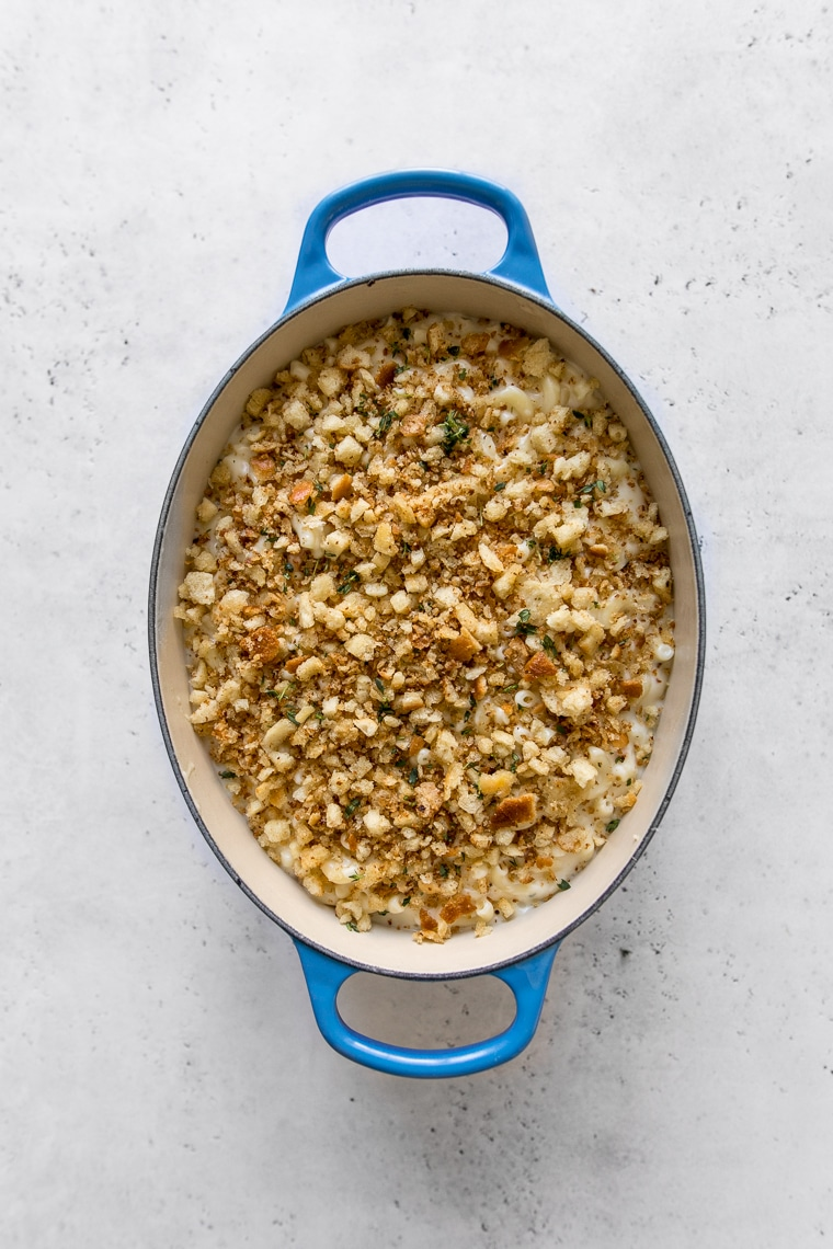 Creamy Baked Mac and Cheese with Bread Crumbs on top, served in a blue oval Le Creuset French Oven