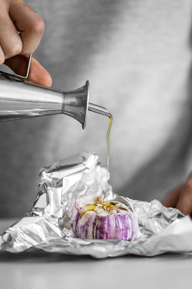 Drizzling olive oil on a head of garlic