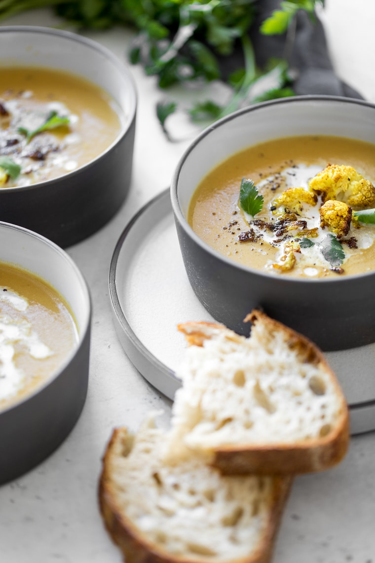 Side angle image of curry cauliflower soup in a black bowl with bread slices