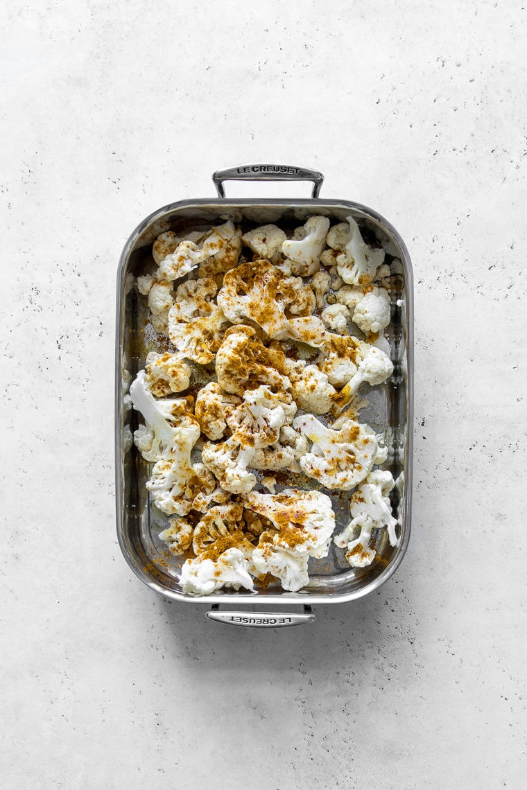 Cauliflower in a roasting pan with curry powder