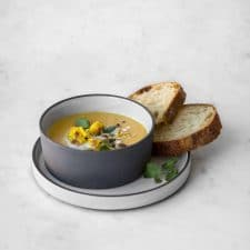 Bowl of curry cauliflower soup with bread