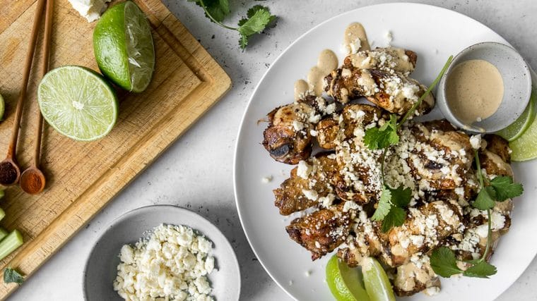 Plate of chicken wings covered in sauce and crumbled cheese next to a cutting board with limes and cotija cheese