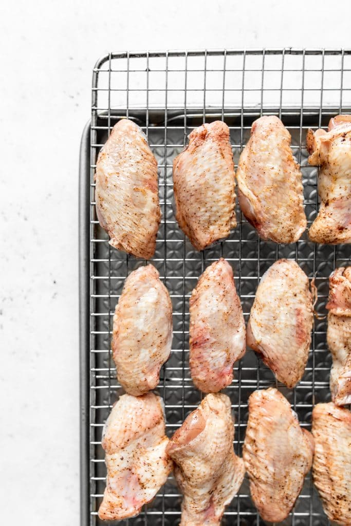Raw Chicken wings on a wire cooling rack