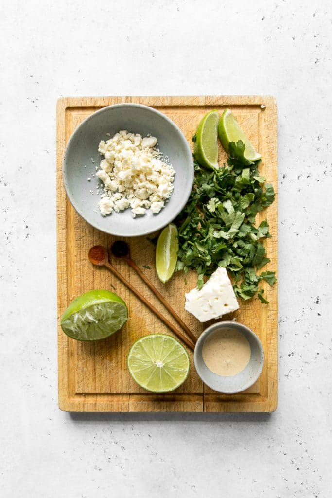 Cutting board with cotija cheese, chopped cilantro, limes, and sauce