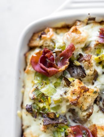 Close up of breakfast casserole with mushrooms and leeks with prosciutto on top