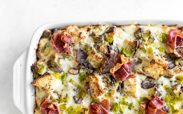 Close up of breakfast strata with leeks, mushrooms, cheese and prosciutto in a white casserole dish