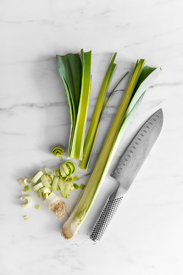 Leeks on a marble table that have been trimmed and are partially chopped, with knife laying next to them