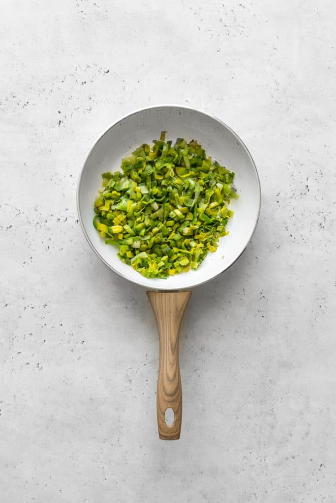 Sauteed leeks in a white skillet