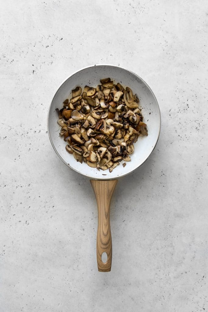 Cooked mushrooms in a white skillet
