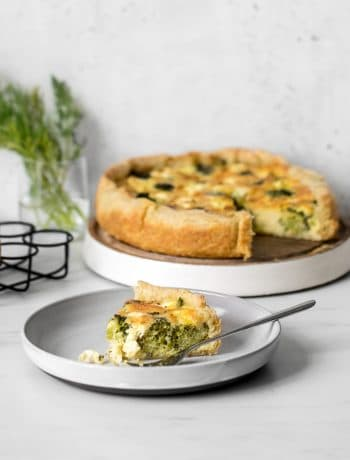 Broccoli and Goat Cheese Quiche on a stand with a slice of quiche on a plate