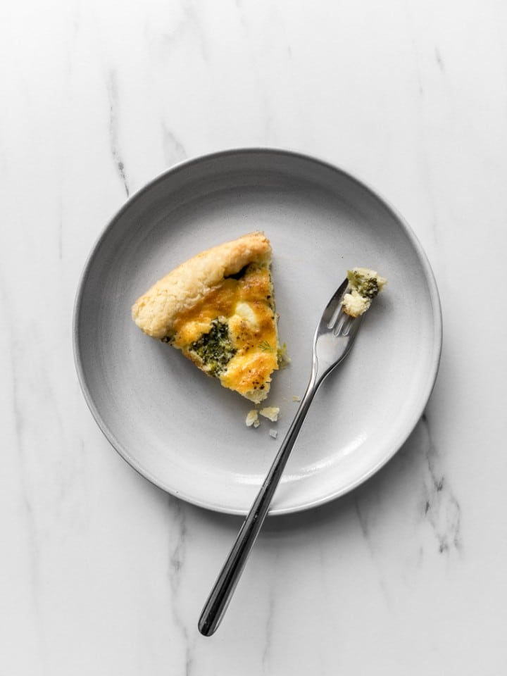 A slice of broccoli and cheese quiche with a bite taken out