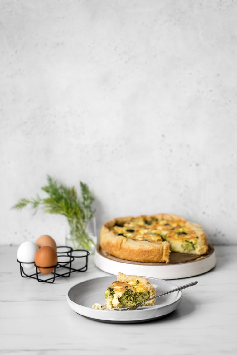 Deep dish quiche with a slice out of it, eggs in an egg holder and a slice of quiche on a table