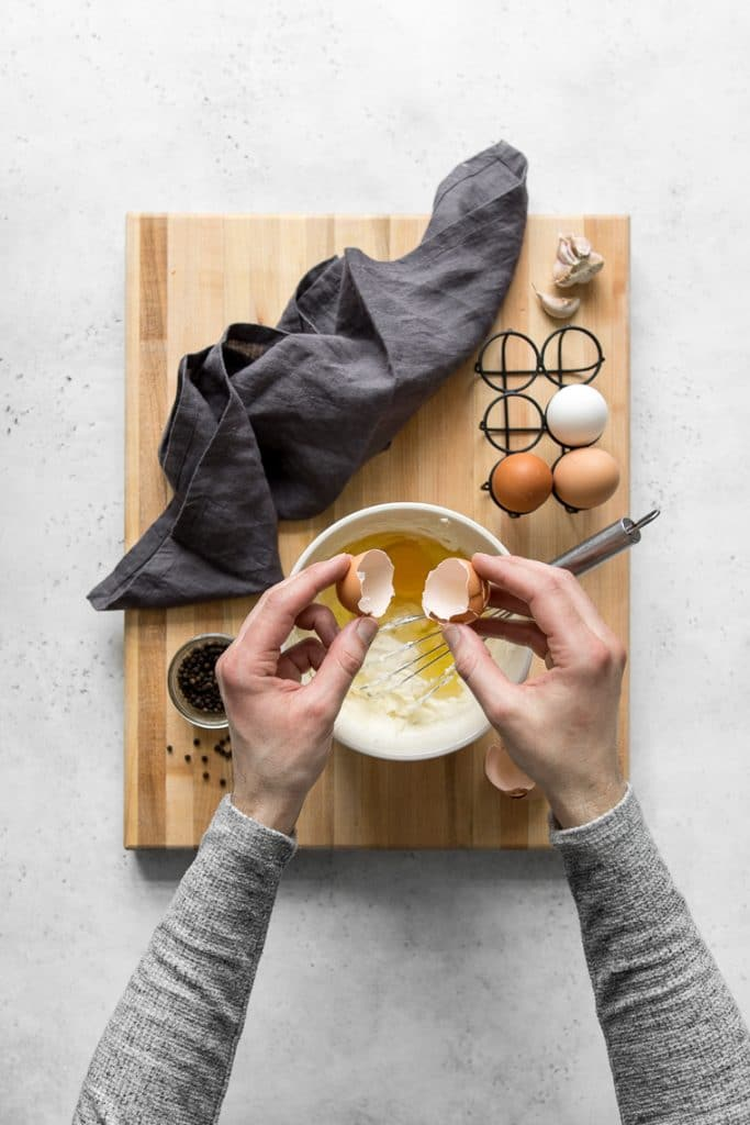Hands cracking eggs into a bowl with goat cheese and cream
