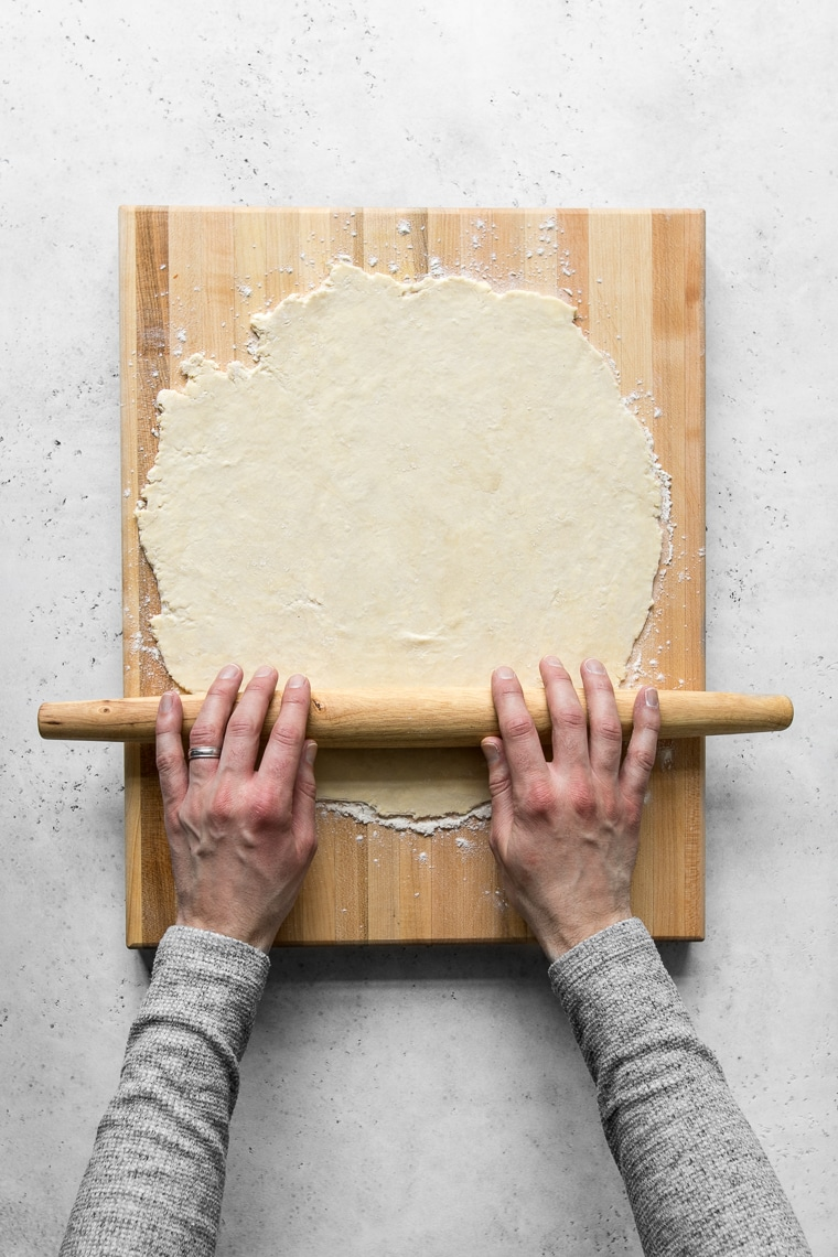 Hands rolling dough on a wooden cutting board