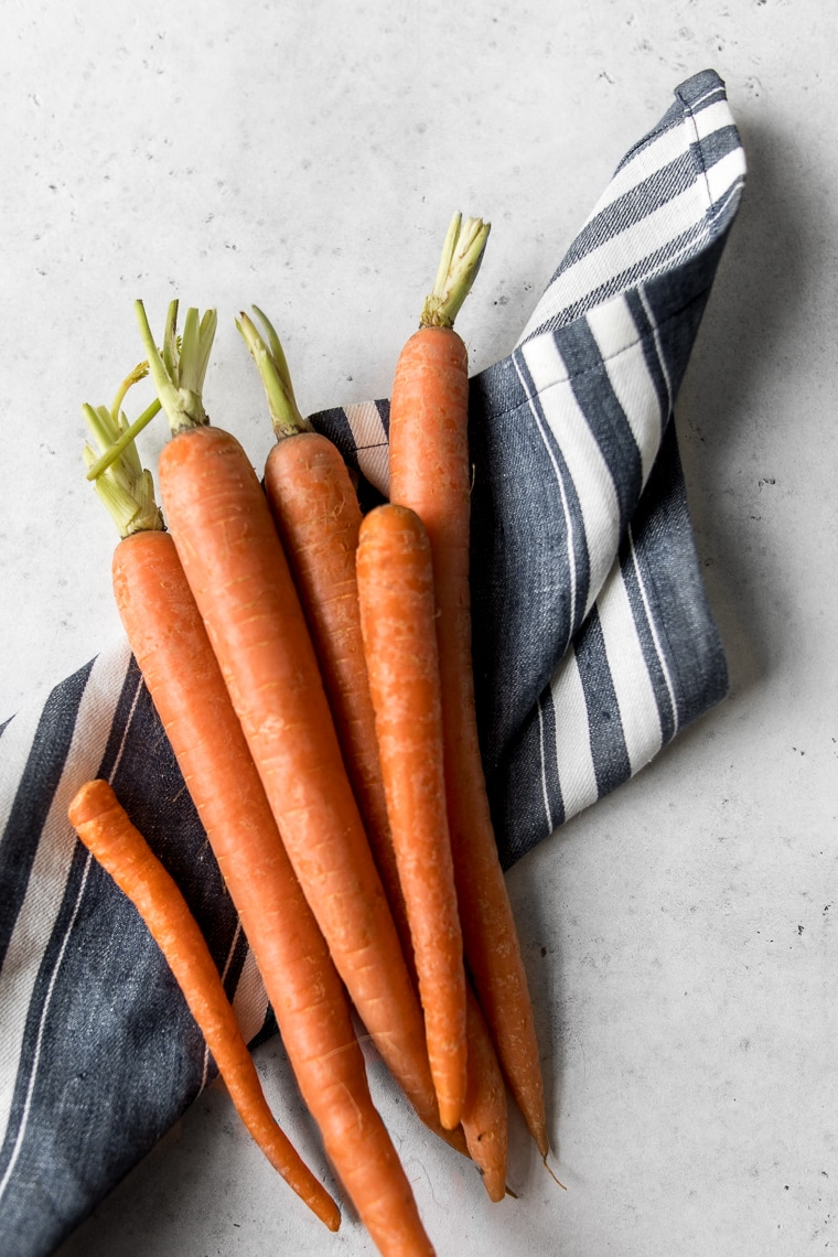 Raw carrots on a blue and white striped towel