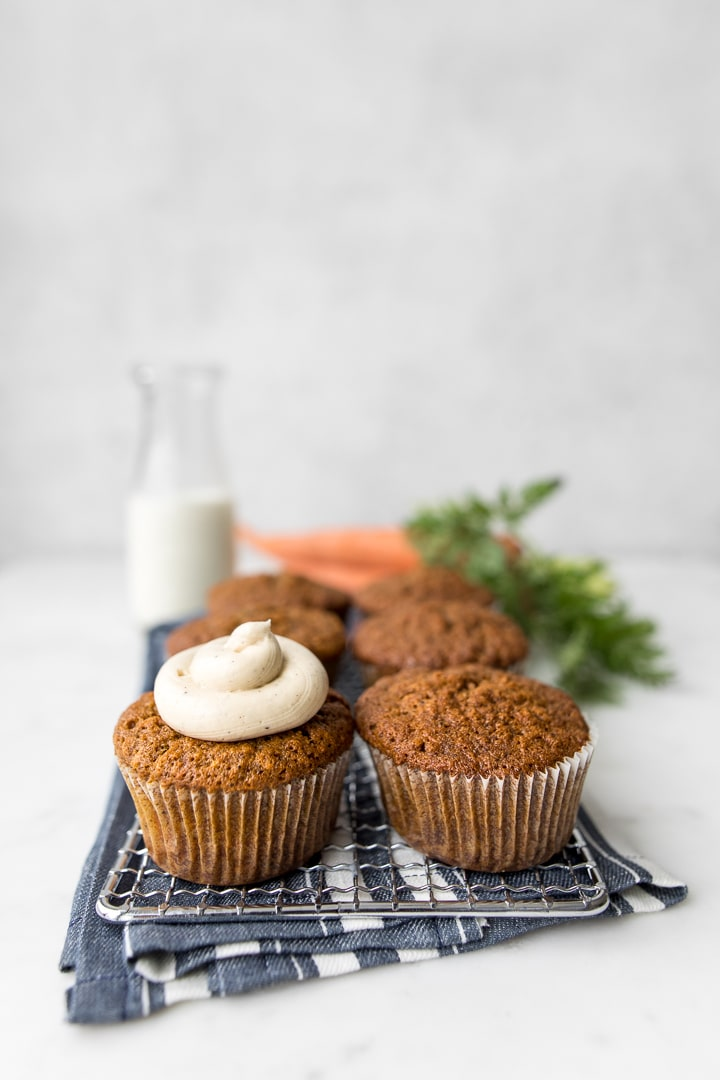 4 carrot cake muffins, one frosted with a jar of milk and fresh carrots